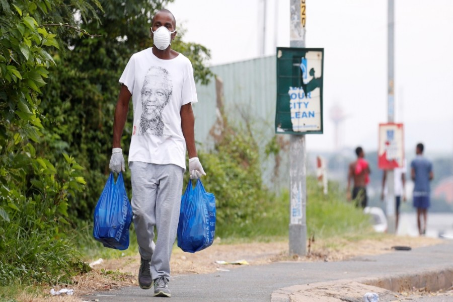 A man carries home groceries during a nationwide lockdown in an attempt to contain the coronavirus disease (COVID-19) outbreak in Umlazi township near Durban, South Africa [Rogan Ward/Reuters]