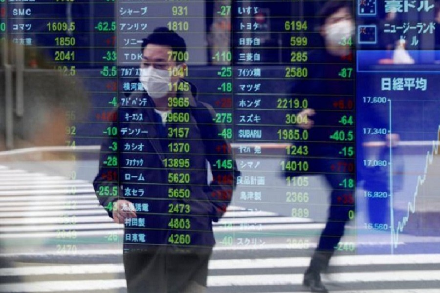 Passersby wearing protective face masks following an outbreak of the coronavirus disease (COVID-19) are reflected on a screen displaying stock prices outside a brokerage in Tokyo, Japan, March 17, 2020. —Reuters