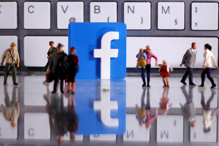 A 3D printed Facebook logo is placed between small toy people figures in front of a keyboard in this illustration taken on April 12, 2020 — Reuters