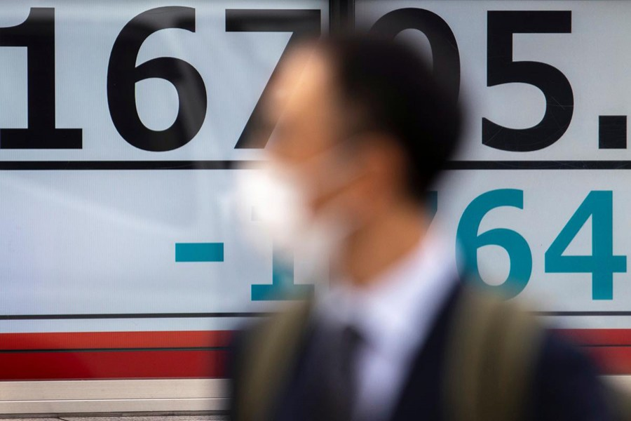 A man wearing a protective face mask, following an outbreak of coronavirus (COVID-19), walks past a screen showing the Nikkei index outside a brokerage in Tokyo, Japan on March 13, 2020 — Reuters/Files
