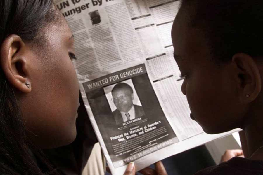 """Readers looking at a newspaper June 12, 2002 in Nairobi carrying the photograph of Rwandan Felicien Kabuga wanted by the United States. The United States published a """"wanted"""" photograph in Kenyan newspapers of the businessman accused of helping finance the 1994 killings in Rwanda. –Reuters Photo"""