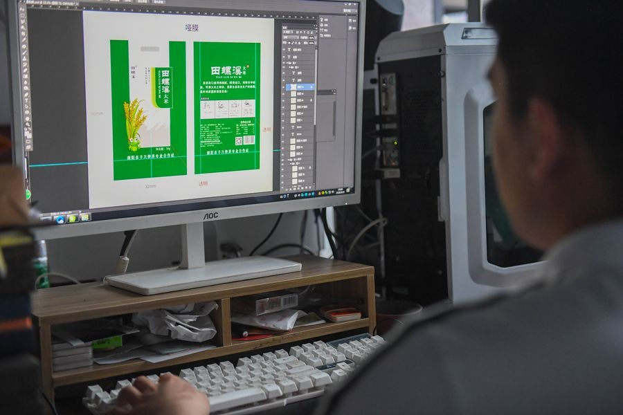 A staff member designs the package for agricultural products at the Liuyang e-commerce business poverty alleviation service center in Liuyang, central China's Hunan Province, May 15, 2020. (Xinhua/Chen Zeguo)