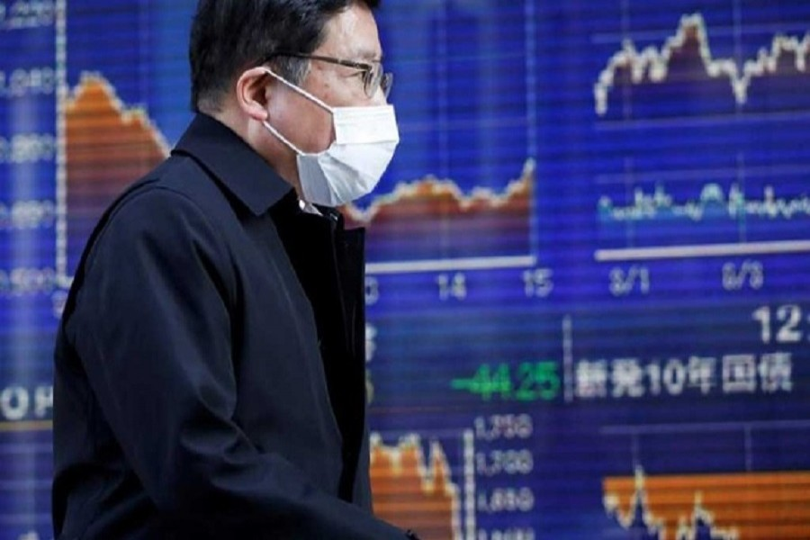 A passerby wearing a protective face mask, following an outbreak of the coronavirus, walks past an electronic board showing the graphs of the recent movements of Japan's Nikkei share average outside a brokerage in Tokyo, Japan, March 06, 2020. — Reuters/Files