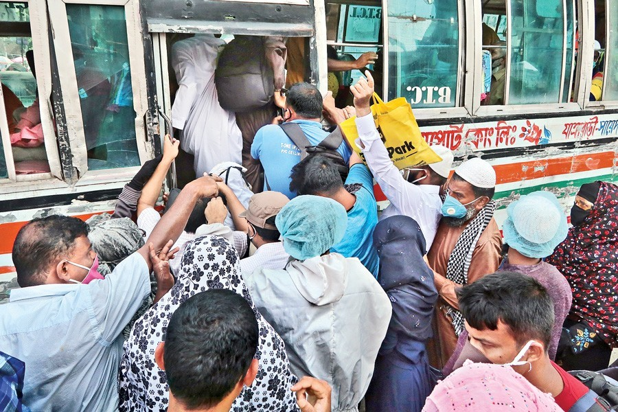 Ignoring health safety norms amid coronavirus outbreak, passengers scramble to get on a local bus at Jatrabari in the city on Monday, the first day of resumption of bus services after over two-month shutdown — FE photo by Shafiqul Alam