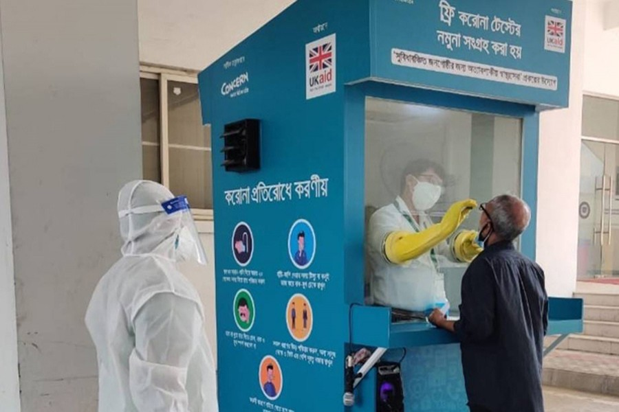 A healthcare worker takes a swab sample from a man at the one-stop digital booth for COVID-19 screening and testing – first of its kind in Bangladesh, at Mugda Medical College Hospital in Dhaka — Collected