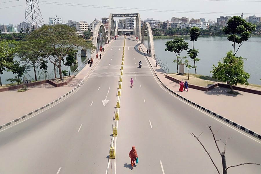 Pedestrians walking along an almost empty street in Hatirjheel area in Dhaka during a lockdown imposed due to the coronavirus