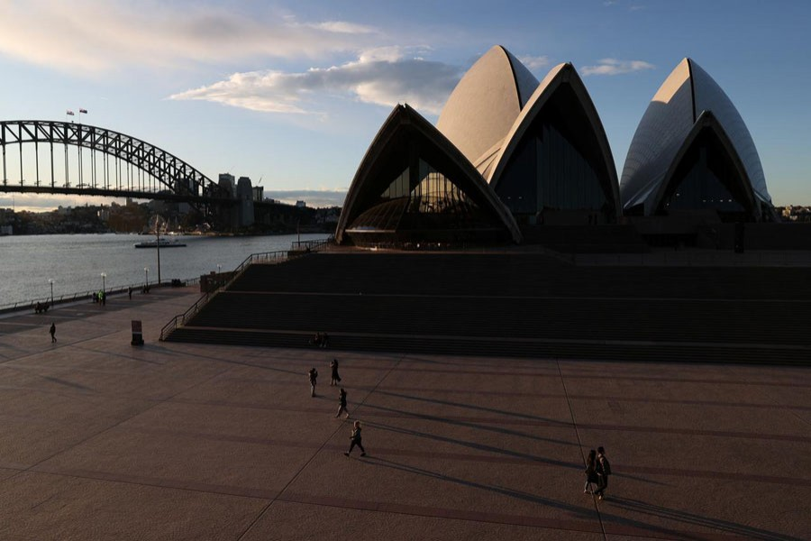 People are seen walking in front of the Sydney Opera House and Sydney Harbour Bridge following the easing of restrictions implemented to curb the spread of the coronavirus disease (COVID-19) in Sydney, Australia, June 23, 2020. REUTERS/Loren Elliott/File photo