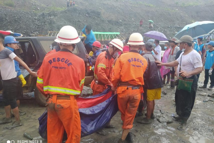 Rescue workers carry a dead body following a landslide at a mining site in Phakant, Kachin State City, Myanmar on July 2, 2020, in this picture obtained from social media — MYANMAR FIRE SERVICES DEPARTMENT via REUTERS