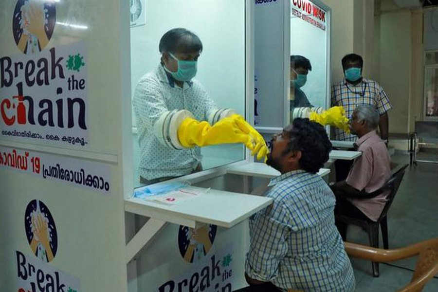 Medical staff members of a government-run medical college collect swabs from people to test for coronavirus disease (Covid-19) at a newly installed Walk-In Sample Kiosk in Ernakulam in the southern state of Kerala, India on April 6, 2020 — Reuters/Files