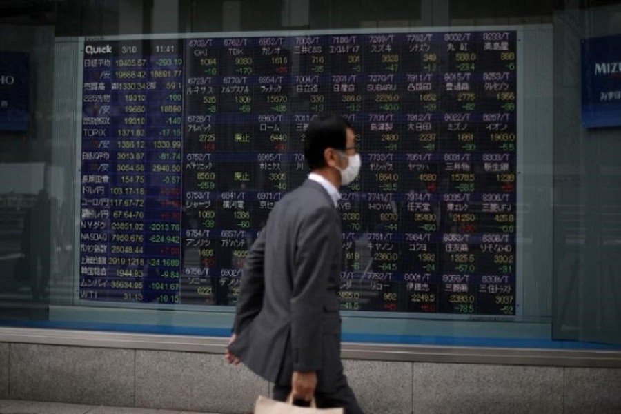 A man wearing a protective face mask, following an outbreak of the coronavirus disease (COVID-19), walks in front of a stock quotation board outside a brokerage in Tokyo, Japan, March 10, 2020 — Reuters/Files