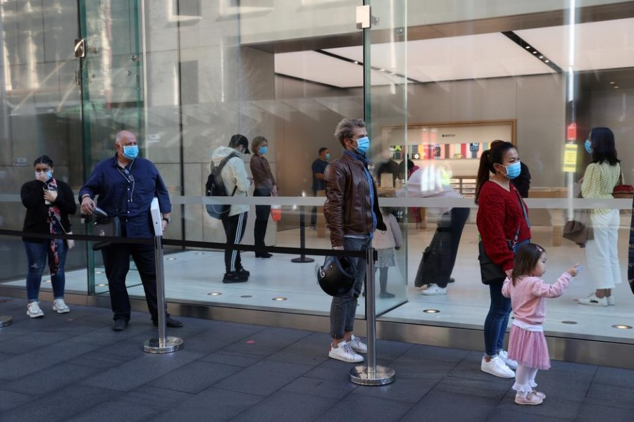 People wearing protective face masks practice social distancing while waiting to enter an Apple store on the first day of New South Wales' further eased coronavirus disease (Covid-19) restrictions in Sydney, Australia on July 1, 2020 — Reuters/Files