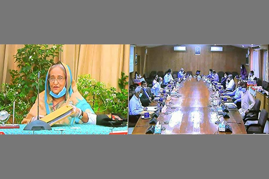 Prime Minister Sheikh Hasina presiding over the cabinet meeting through a videoconference Ganabhaban, while ministers and secretaries attended the meeting from the Bangladesh Secretariat in Dhaka on Monday –BSS photo