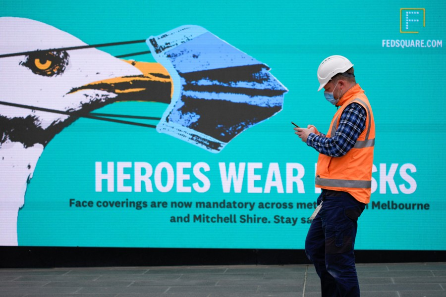 An essential worker wearing a face mask walks past a 'Heroes Wear Masks' sign in Melbourne after it became the first city in Australia to enforce mask-wearing in public as part of efforts to curb a resurgence of the coronavirus disease (Covid-19) on July 23, 2020 — Reuters photo
