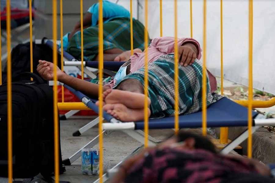 Migrant workers taking rest at a swab isolation facility as they wait for their test results at a dormitory, amid the coronavirus disease (COVID-19) outbreak in Singapore May 15, 2020 –Reuters Photo