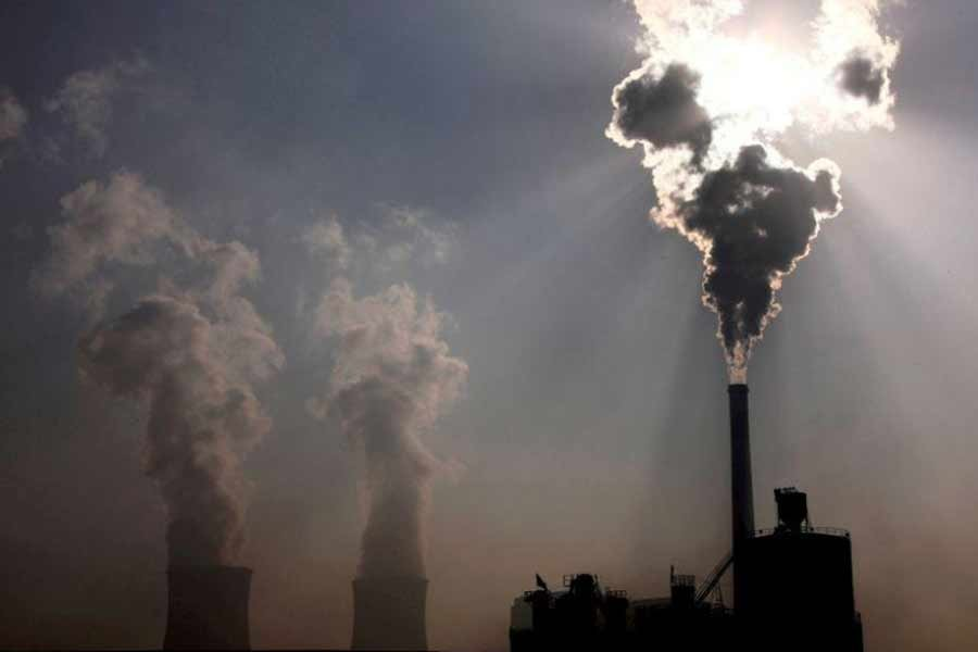 A coal-burning power plant can be seen behind a factory in the city of Baotou, in China's Inner Mongolia Autonomous Region –Reuters file photo