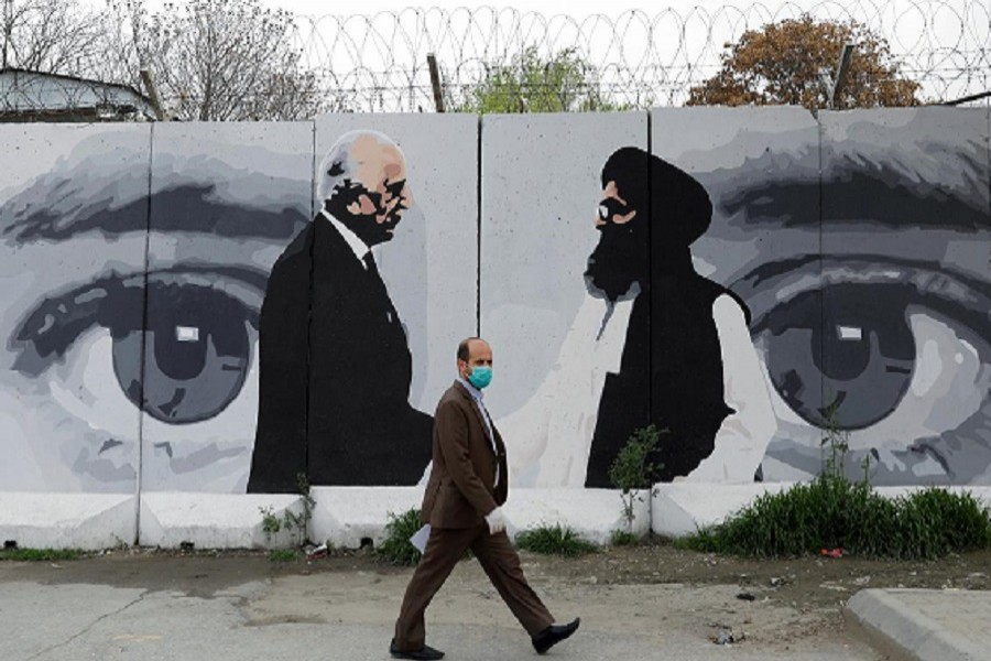 An Afghan man wearing a protective face mask walks past a wall painted with photo of Zalmay Khalilzad, US envoy for peace in Afghanistan, and Mullah Abdul Ghani Baradar, the leader of the Taliban delegation, in Kabul, Afghanistan, April 13, 2020 — Reuters/Files