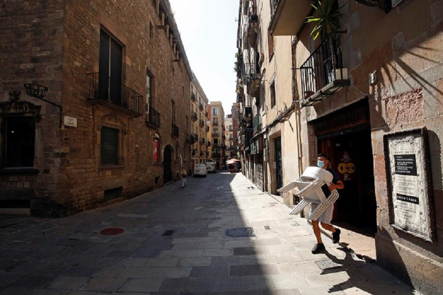 A staff member of a bar carries chairs, amid the coronavirus disease (Covid-19) outbreak, in the Gothic quarter in Barcelona, Spain, July 27, 2020 — Reuters/Files