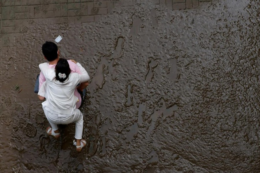 A man crosses a mud-covered trail carrying his wife on his back at a flooded Han River park in Seoul, South Korea, August 04, 2020. REUTERS