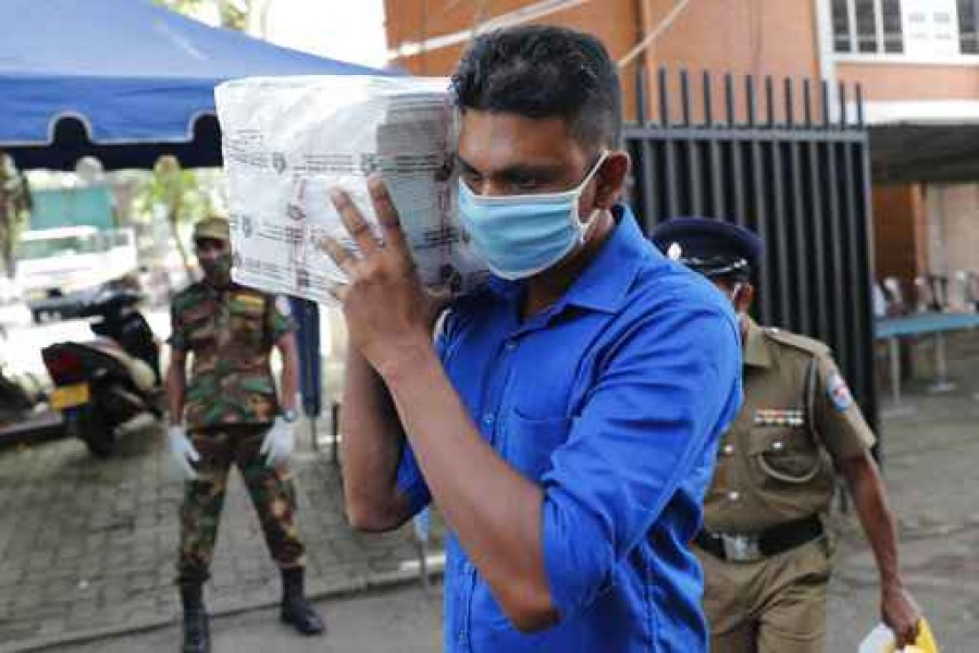 A Sri Lankan polling officer carries election material to dispatch them to polling centers ahead of the parliamentary elections in Colombo, Sri Lanka, Tuesday, Aug. 4, 2020 - AP