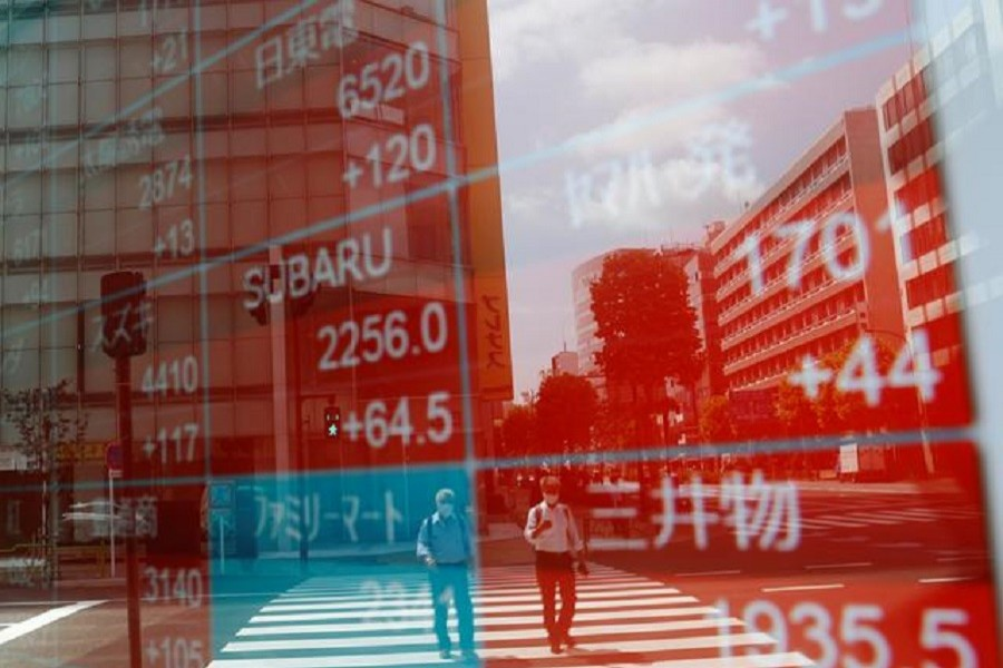 People wearing protective masks, following the coronavirus disease (Covid-19) outbreak, are reflected on a screen showing stock prices outside a brokerage in Tokyo, Japan, August 31, 2020 — Reuters/Files
