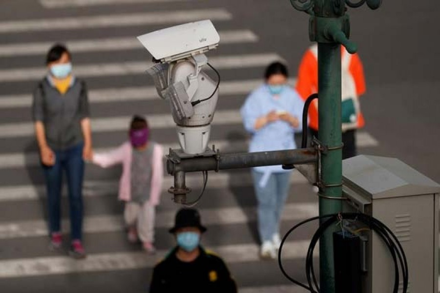 ILE PHOTO: A CCTV security surveillance camera overlooks a street as people walk following the spread of the coronavirus disease (COVID-19) in Beijing, China May 11, 2020. REUTERS/Thomas Peter