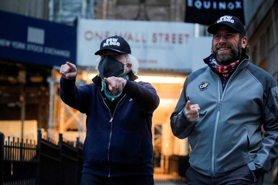 Trader Peter Tuchman and specialist trader Michael Pistillo greeting friends as they exit the New York Stock Exchange, (NYSE) wearing DOW 30,000 hats, in New York last month –Reuters file photo