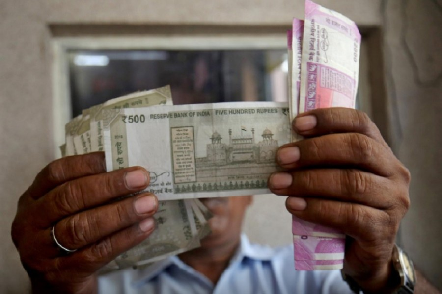 A cashier checks Indian rupee notes inside a room at a fuel station in Ahmedabad, India, September 20, 2018 - Reuers file photo