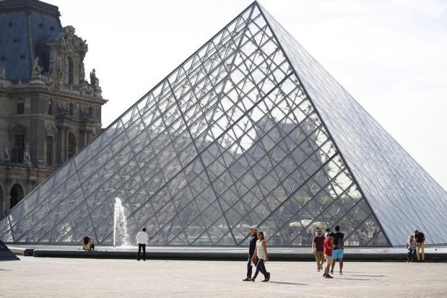 Tourists stand in front of the Louvre Pyramid designed by Chinese-born US Architect Ieoh Ming Pei in Paris, France — Reuters/Files