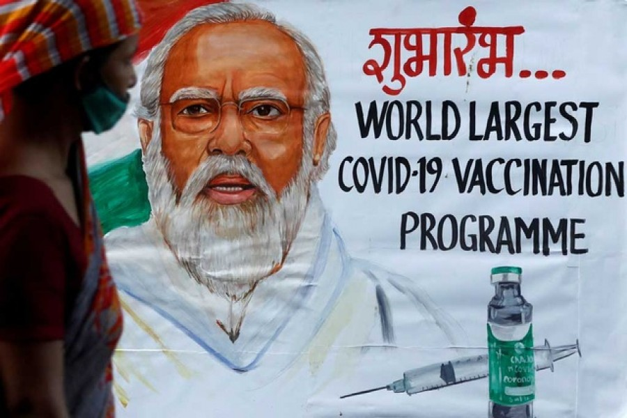 A woman walks past a painting of Indian Prime Minister Narendra Modi a day before the inauguration of the Covid-19 vaccination drive on a street in Mumbai, India, January 15, 2021 — Reuters