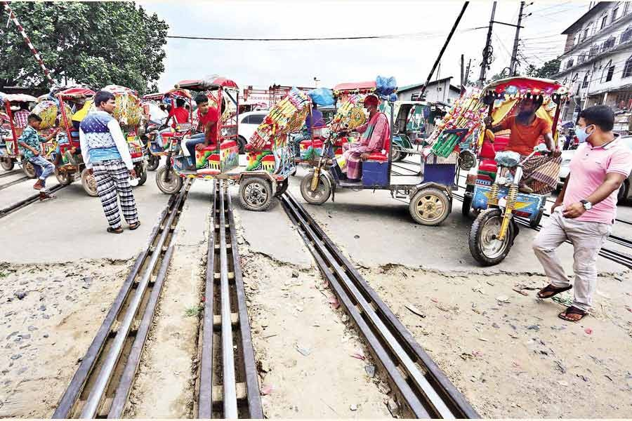 Battery-run tricycles known as easybikes wait for passengers on the level-crossing on the Hajee Camp Road near the Airport Railway Station in the city on Sunday, defying the risk that an accident can happen any time — FE file photo by KAZ Sumon