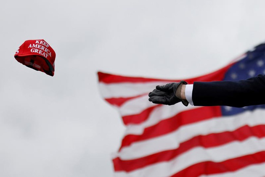 US President Donald Trump tosses out 'Keep America Great' caps as he arrives for a campaign rally at Oakland County International Airport in Waterford Township, Michigan, US on October 30, 2020 — Reuters/Files