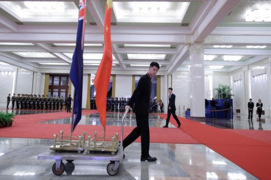 An attendant moves flags of New Zealand and China after a welcome ceremony for Prime Minister Jacinda Ardern at the Great Hall of the People in Beijing, China, April 1, 2019. REUTERS