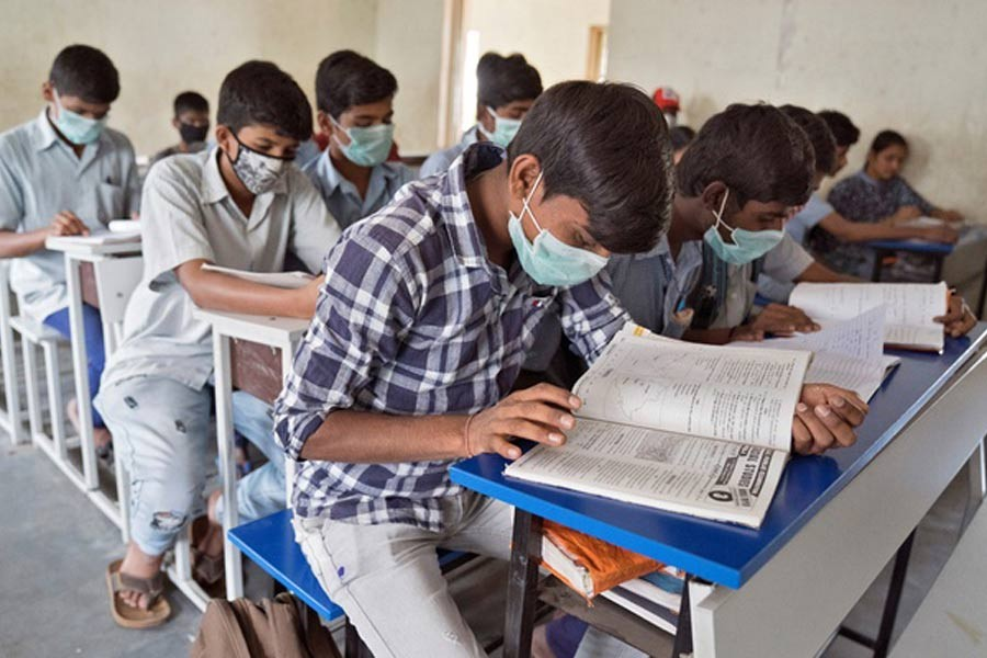 Students wearing protective masks attend a class in a government-run school in Hyderabad, India, March 5, 2020. Reuters