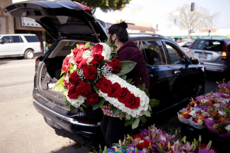 A woman lifts a funeral display into a car in the flower district as the coronavirus disease (Covid-19) outbreak continues, ahead of Valentine's Day in Los Angeles, California, US, February 4, 2021. REUTERS/Lucy Nicholson