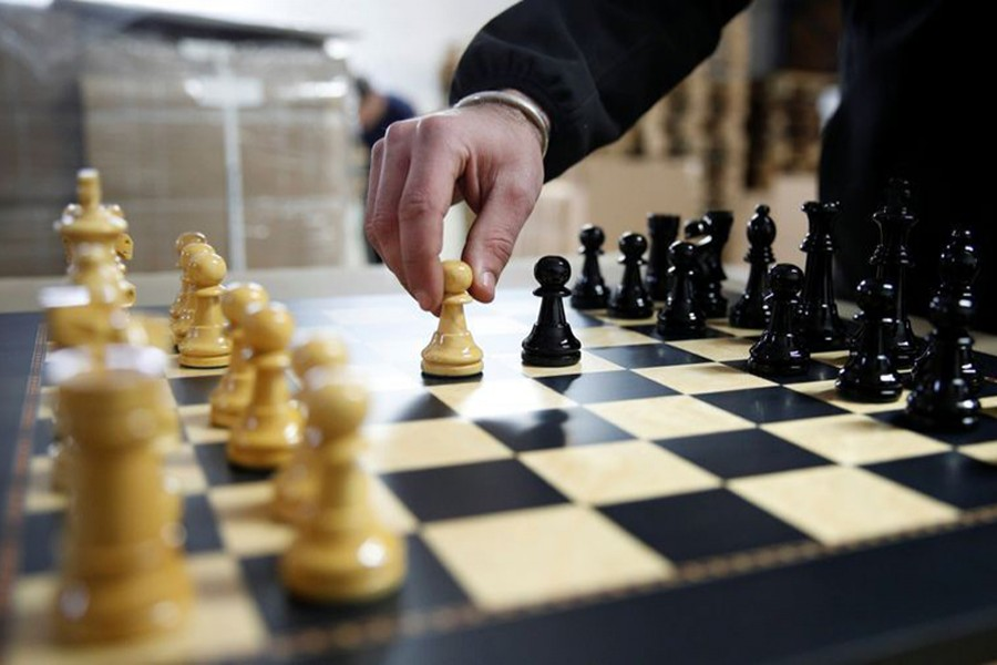 """David Ferrer moves a chess pawn on a chessboard at the Rechapados Ferrer factory of which products have appeared in the Netflix series """"The Queen's Gambit"""", in La Garriga, north of Barcelona, Spain on February 11, 2021 — Reuters photo"""