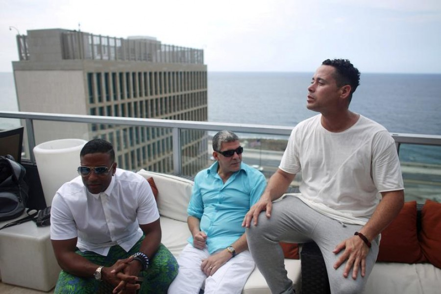 FILE PHOTO: (L-R) Members of the Cuban fusion group Orishas - Yotuel, Roldan and Ruzzo - give an interview from the top of a building in Havana, Cuba, June 22, 2016. REUTERS/Alexandre Meneghini/File Photo