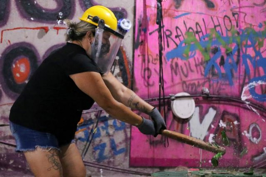 Luciana Holanda smashes a bottle at the Rage Room, a place where people can destroy objects to vent their anger, in Sao Paulo, Brazil, February 19, 2021. REUTERS/Carla Carniel