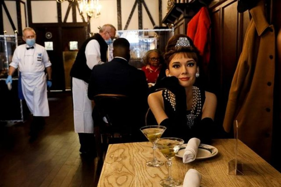 Madame Tussauds's wax figure of Audrey Hepburn sits at an empty table to comply with coronavirus disease (COVID-19) social distancing requirements in a dining room at Peter Luger Steak House in Brooklyn, New York ,US, February 26, 2021. REUTERS/Brendan McDermid