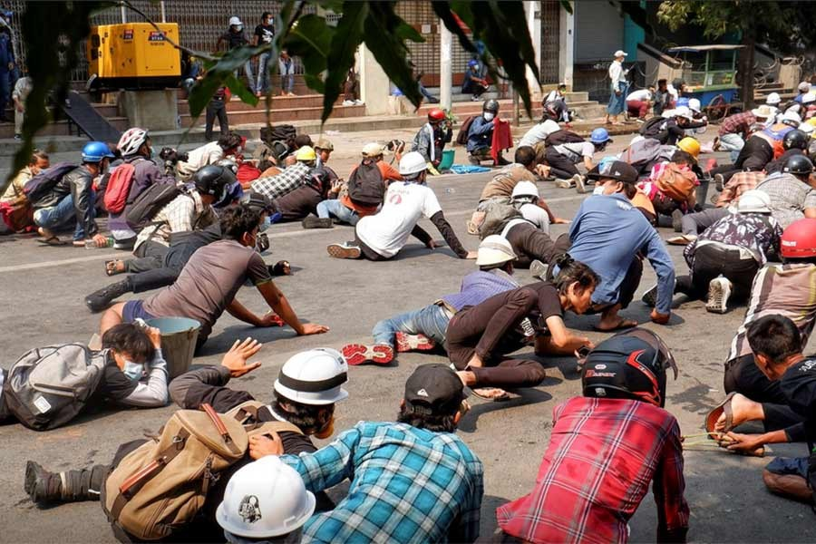 Protesters lie on the ground after police open fire to disperse an anti-coup protest in Mandalay of Myanmar on Wednesday -Reuters Photo