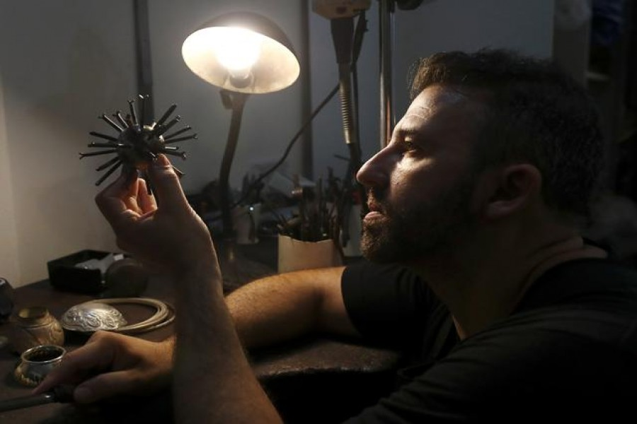 """Argentine artist Marcelo Toledo works on an art piece depicting a coronavirus virion made from iron that will be part of the """"Museum of the After"""", at his workshop in Buenos Aires, Argentina March 4, 2021. REUTERS/Agustin Marcarian"""