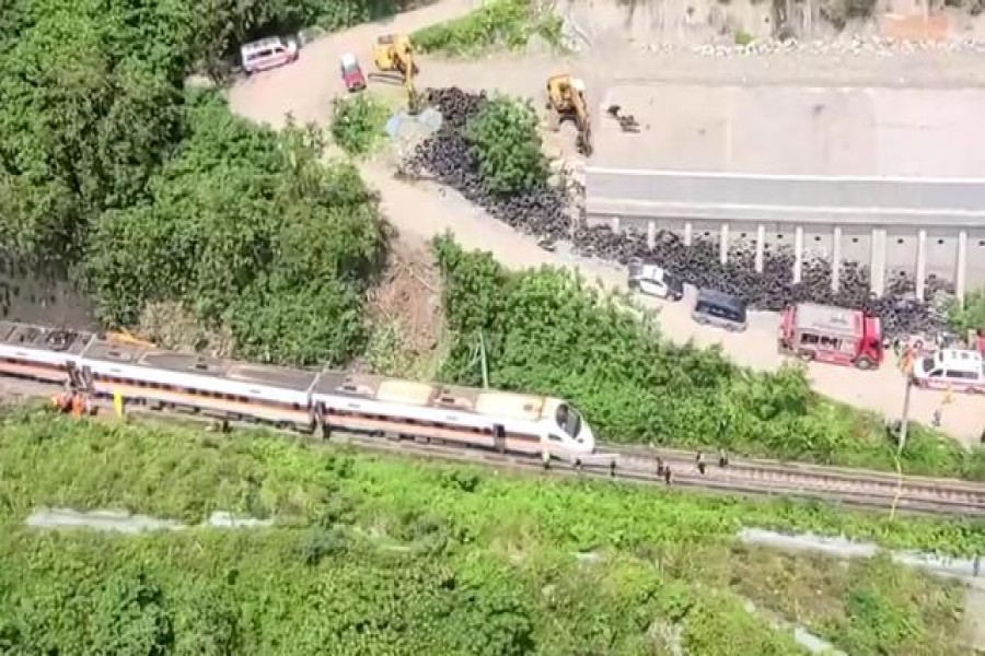 Rescue workers walk next to a damaged train which derailed in a tunnel north of Hualien, Taiwan April 2, 2021, in this still image taken from video. FTV via Reuters