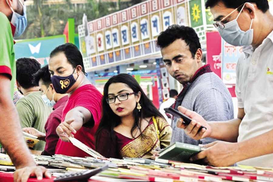 Without following health guidelines amid the surging pandemic, people flicking through books at a stall at the Amar Ekushey Book Fair at the Suhrawardy Udyan in the city on Friday —Focus Bangla Photo
