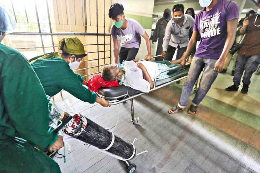With the Oxygen mask on, a critical patient, who got admitted to the Mugda Medical College and Hospital in the city on Tuesday with respiratory symptoms, being hurriedly moved to the designated ward by his relatives and the hospital staff — FE photo by KAZ Sumon