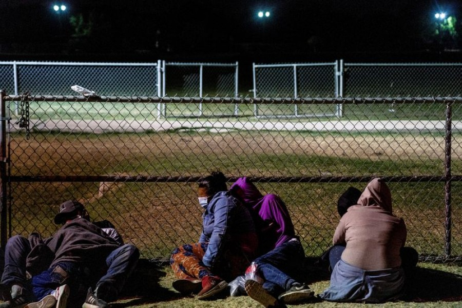 Asylum-seeking migrants' families rest on the ground while waiting to be transported by the US Border Patrols after crossing the Rio Grande River into the United States from Mexico in La Joya, Texas, U.S., April 7, 2021. REUTERS/Go Nakamura/File Photo