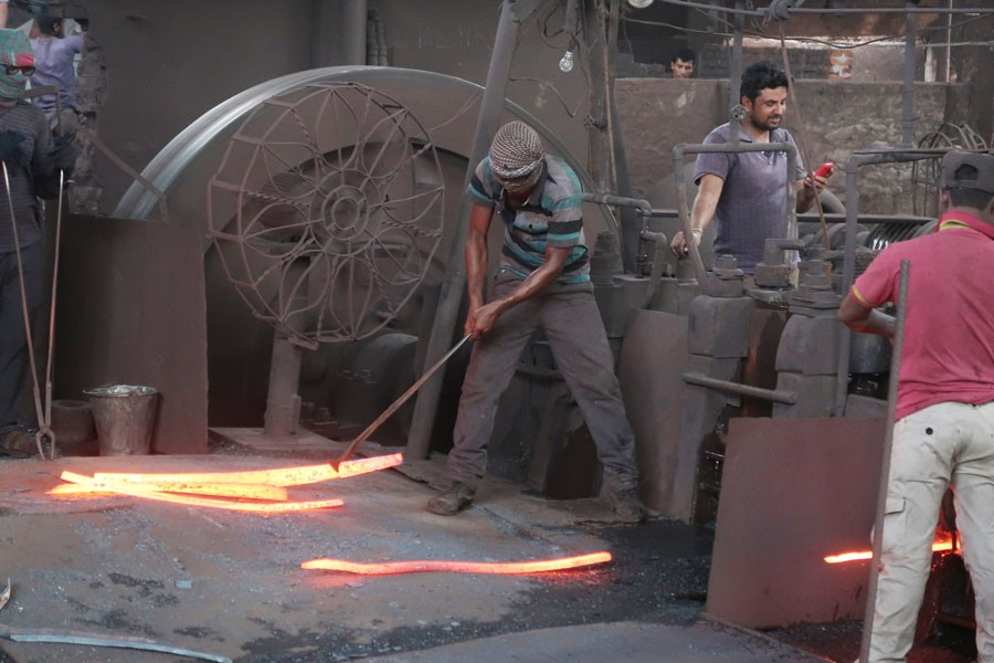 Workers at a re-rolling factory in Dhaka—FE Photo