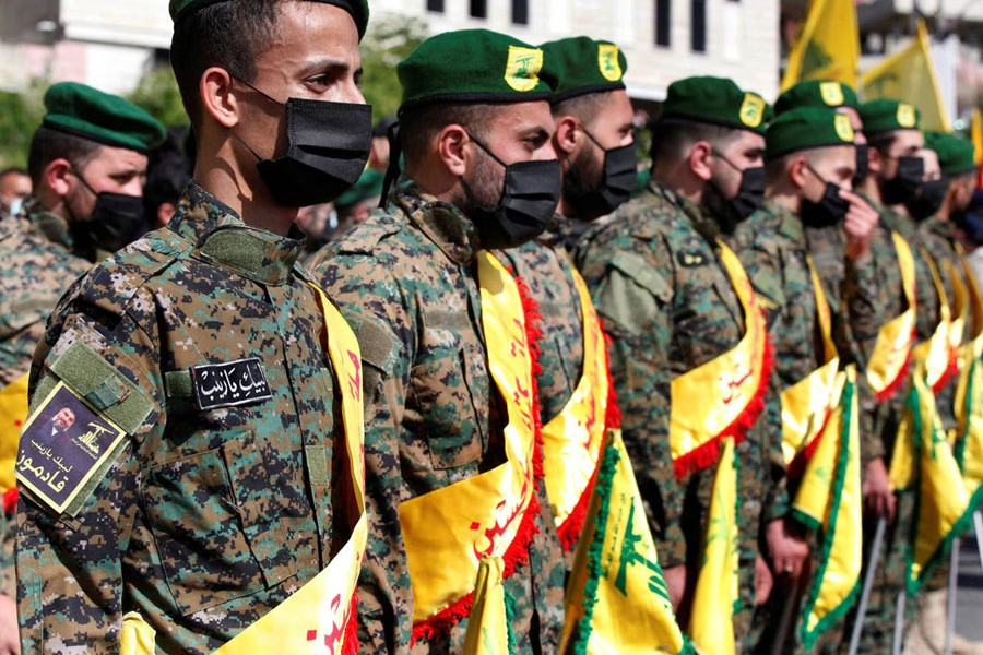 Hezbollah fighters attend the funeral procession of a comrade in Adloun, Lebanon, in May