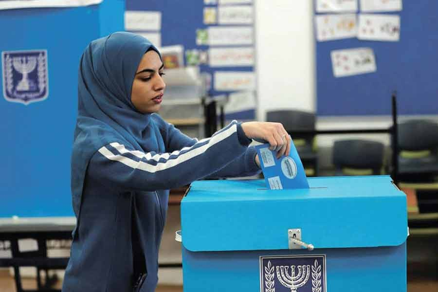 An Arab Israeli woman casts her ballot in the election at a polling station in Tamra, last March