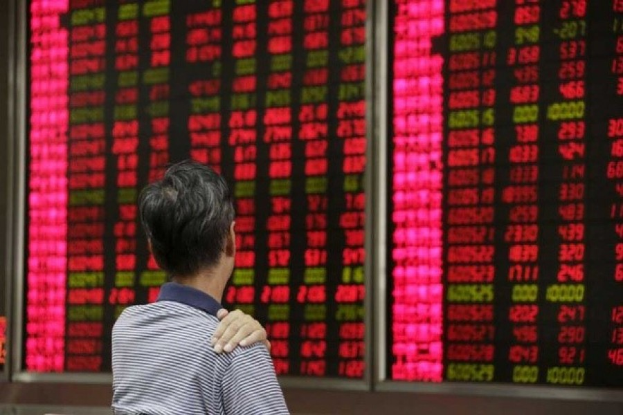 An investor looks at an electronic board showing stock information at a brokerage house in Beijing, August 27, 2015 — Reuters