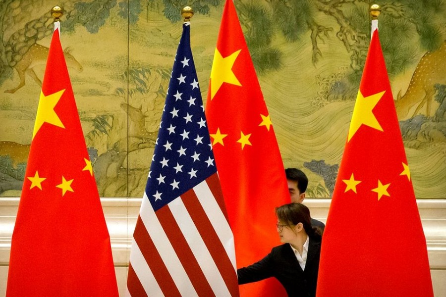Chinese staffers adjust US and Chinese flags before the opening session of Sino-US trade negotiations in Beijing on February 14, 2019 — Pool via Reuters