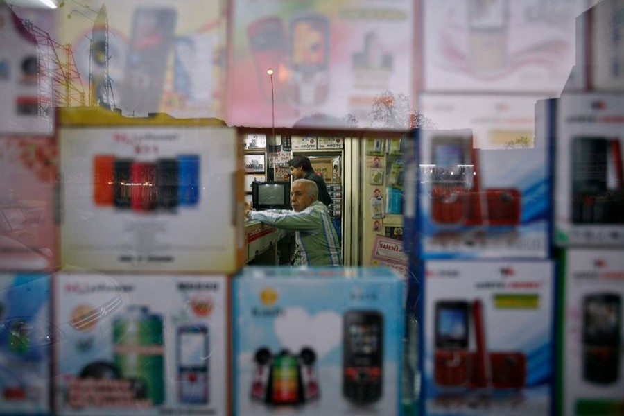 A vendor waits for customers inside his shop that sells mobile phones at Surat, in the western Indian state of Gujarat on January 4, 2013 — Reuters/Files